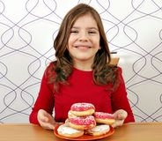 Little girl with sweet donuts Stock Photos