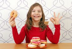 Little girl with sweet donuts and ok hand sign Royalty Free Stock Images
