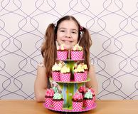 Little girl with sweet muffins on table Royalty Free Stock Image