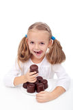 Little girl with a sweet tooth. Eating large chocolate coated cookies Royalty Free Stock Images