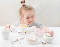 Little girl with sweets around her Stock Photography