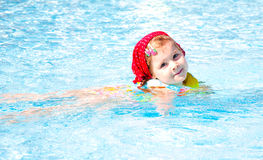 Little girl swiming. Little girl in red hood  swiming in the pool Royalty Free Stock Photography