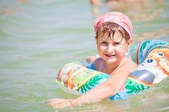 Little girl swimming Stock Image