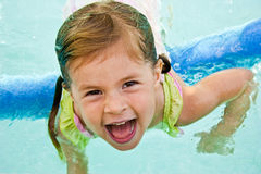 Little girl swimming Stock Images
