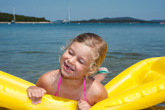 Little girl is swimming with air mattress in blue sea Royalty Free Stock Images