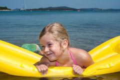 Little girl is swimming with air mattress in blue sea Stock Photo
