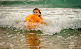 Little girl swimming with the ball in the ocean on the waves Royalty Free Stock Photo