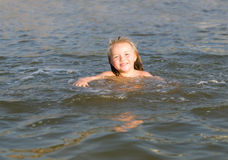 Little girl swimming at the beach Stock Image