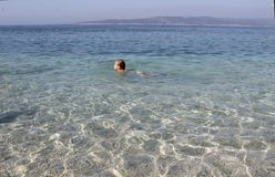 The little girl is swimming in the crystal clear sea. Croatia royalty free stock photography