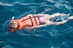 Little girl swimming in diving mask. Little girl swimming in life jacket and diving mask and snorkel Stock Image