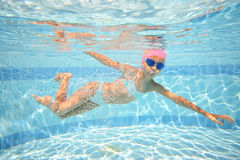 Little girl in swimming goggles swimming underwater Stock Image