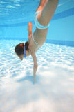 Little girl in swimming goggles swimming underwater royalty free stock photos