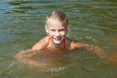 Little girl swimming in lake Stock Image