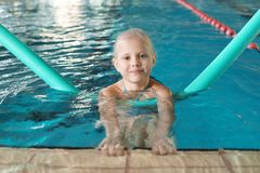 Little girl with swimming noodle. In indoor pool stock images