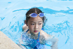 Little girl in swimming pool. 9-year old little asian girl in swimming pool Stock Photo