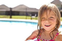 Little girl at swimming pool. A little girl smiling in front of a swimming pool Royalty Free Stock Images