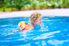 Little girl swimming in a pool Stock Photo