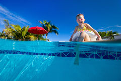 Little girl at swimming pool. Adorable little girl at swimming pool having fun during summer vacation Royalty Free Stock Image