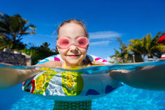 Little girl in swimming pool. Adorable little girl at swimming pool having fun during summer vacation Royalty Free Stock Image