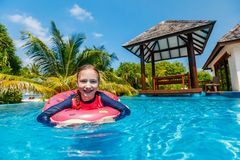 Little girl in swimming pool. Adorable little girl at swimming pool having fun during summer vacation Stock Photos