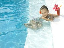 Girl in the swimming pool. Little girl in the swimming pool with cocktail Royalty Free Stock Photos