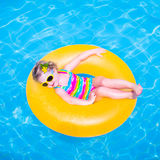 Little girl in a swimming pool. Cute funny little toddler girl in a colorful swimming suit and sun glasses relaxing on an inflatable toy ring floating in a pool Stock Images