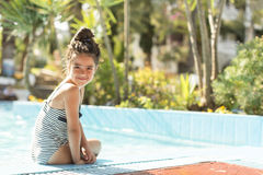 Little girl by the swimming pool. Cute little girl sitting by the swimming pool royalty free stock images