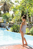 Little girl by the swimming pool. Cute little girl standing by the swimming pool stock image