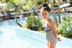 Little girl by the swimming pool. Cute little girl standing by the swimming pool royalty free stock images