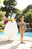 Little girl by the swimming pool. Cute little girl standing by the swimming pool stock photography