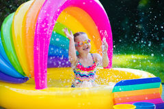 Little girl in swimming pool. Little girl with goggles playing in inflatable baby pool. Kids swim and splash in colorful garden play center. Children with water Royalty Free Stock Photos