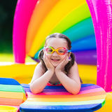 Little girl in swimming pool. Little girl with goggles playing in inflatable baby pool. Kids swim and splash in colorful garden play center. Children with water Royalty Free Stock Photography