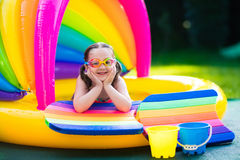 Little girl in swimming pool. Little girl with goggles playing in inflatable baby pool. Kids swim and splash in colorful garden play center. Children with water Royalty Free Stock Images