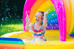 Little girl in swimming pool. Little girl with goggles playing in inflatable baby pool. Kids swim and splash in colorful garden play center. Children with water Stock Photo