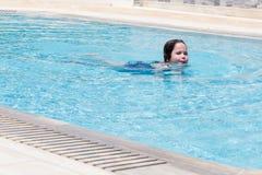 Little girl swimming in a pool. Happy little girl swimming in a pool Royalty Free Stock Photo