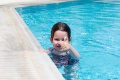 Little girl swimming in a pool. Happy little girl swimming in a pool Royalty Free Stock Photography