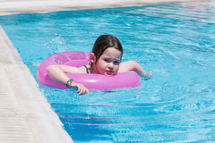 Little girl swimming in a pool Stock Images