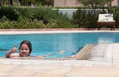 Little girl swimming in a pool Stock Photos