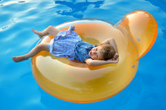 Little girl swimming in the pool on an inflatable chair, bright Royalty Free Stock Photography