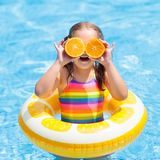 Child in swimming pool. Kid eating orange. Little girl in swimming pool with inflatable toy ring eating orange. Kids swim on summer vacation. Tropical fruit and Royalty Free Stock Photography