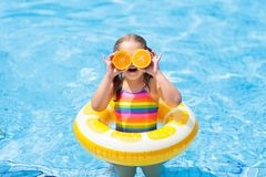 Child in swimming pool. Kid eating orange. Little girl in swimming pool with inflatable toy ring eating orange. Kids swim on summer vacation. Tropical t and Stock Images