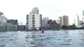 Little girl swimming in a pool with sky scraper city background. stock video footage