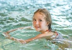 Little girl swimming. Stock Photos