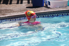 Little girl swimming in pool. Swim lesson in summer, outside pool Royalty Free Stock Image