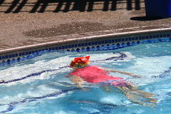 Little girl swimming in pool. Swim lesson in summer, outside pool Stock Photo