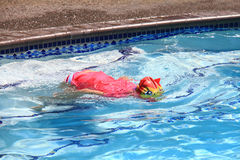 Little girl swimming in pool. Swim lesson in summer, outside pool Stock Image