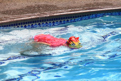 Little girl swimming in pool. Swim lesson in summer, outside pool Stock Images