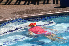 Little girl swimming in pool. Swim lesson in summer, outside pool Royalty Free Stock Photos