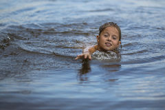 Little girl swimming in the river. Pulls the arm out of the water. Summer. Royalty Free Stock Photos