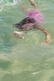 Little girl swimming in the sea under the water in a mask for diving, Royalty Free Stock Photography